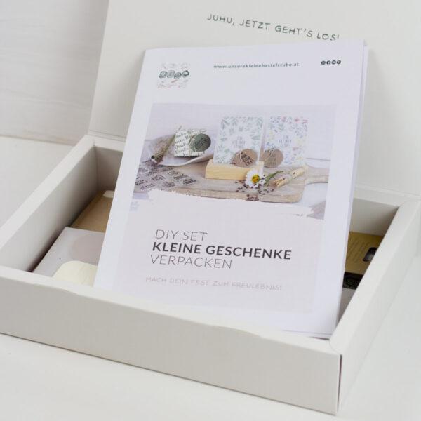 Freulebnis-Box-Kleine-Geschenke-Verpacken-Unsere-kleine-Bastelstube mit Anhänger und kleinen Postkarten mit Wiesenblumen Motiv